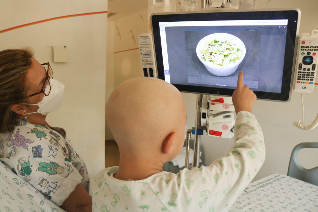 paciente eligiendo el menú en la pantalla de su habitación junto a una enfermera